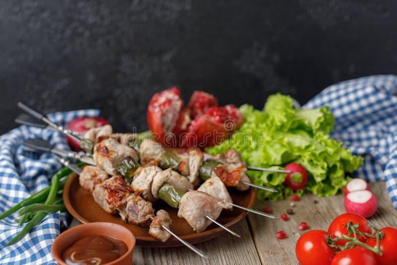 I kebab delicati di carne di maiale sugli spiedi hanno allineato con un piatto degli ortaggi freschi e del melograno maturo Carne immagine stock libera da diritti