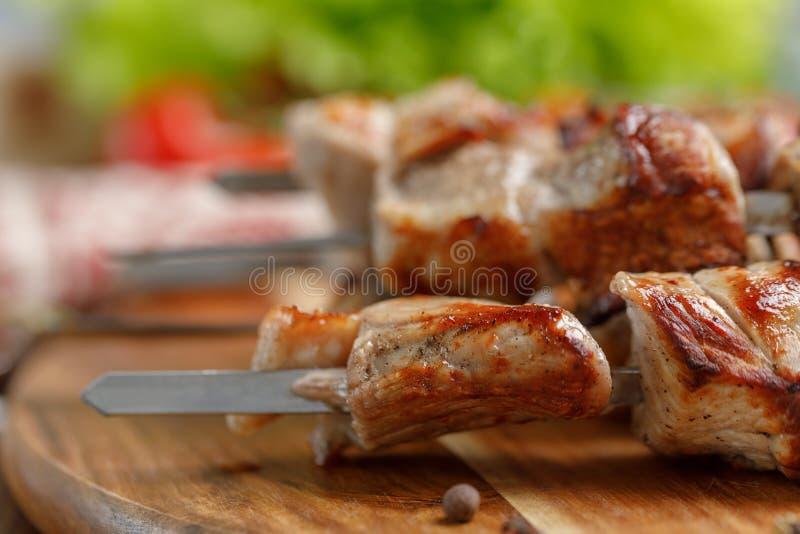 I kebab succosi di carne di maiale hanno cucinato su un fuoco aperto Natura morta appetitosa su un fondo di legno fotografie stock