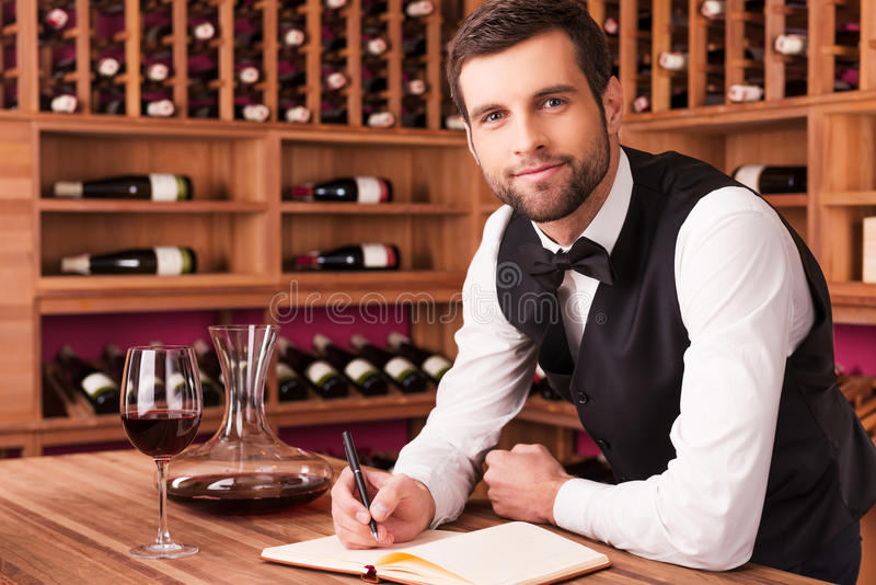 I know everything about wine. Confident male sommelier writing something in his note pad and looking at camera while leaning at the wooden table with wine shelf royalty free stock photos