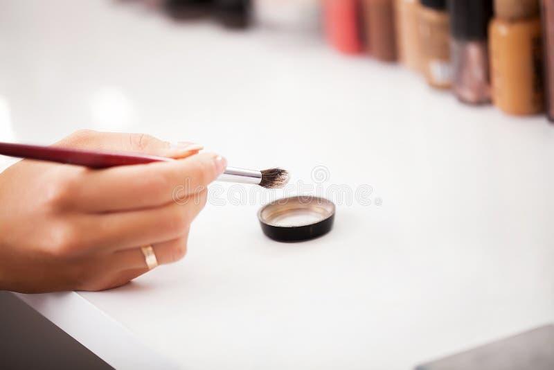 I kulisserna plats: Yrkesmässig sminkkonstnär som gör makeup för yo royaltyfria foton