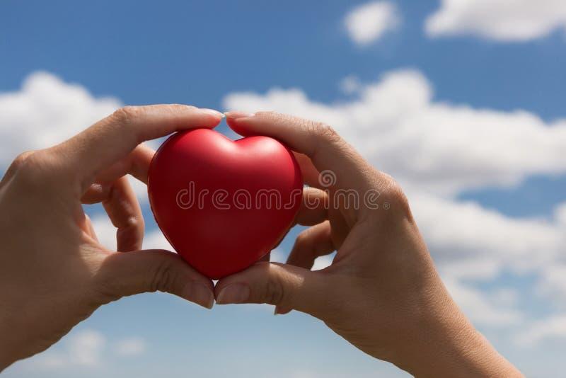 I kvinnliga händer en röd volymetrisk hjärta, som ett symbol av liv och förälskelse, mot den blåa himlen med moln royaltyfri foto
