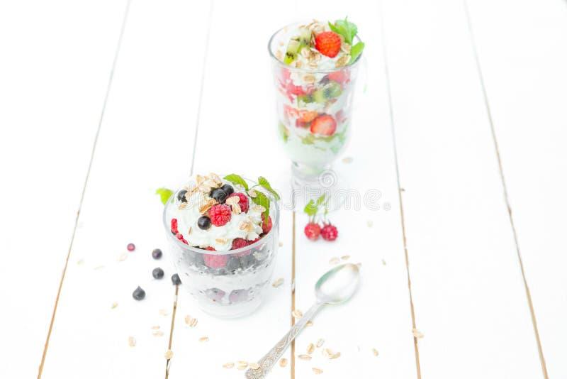 I lager efterrätt med hallonet, jordgubbe, svart vinbär och kiwi, kräm och kex i exponeringsglas arkivbilder
