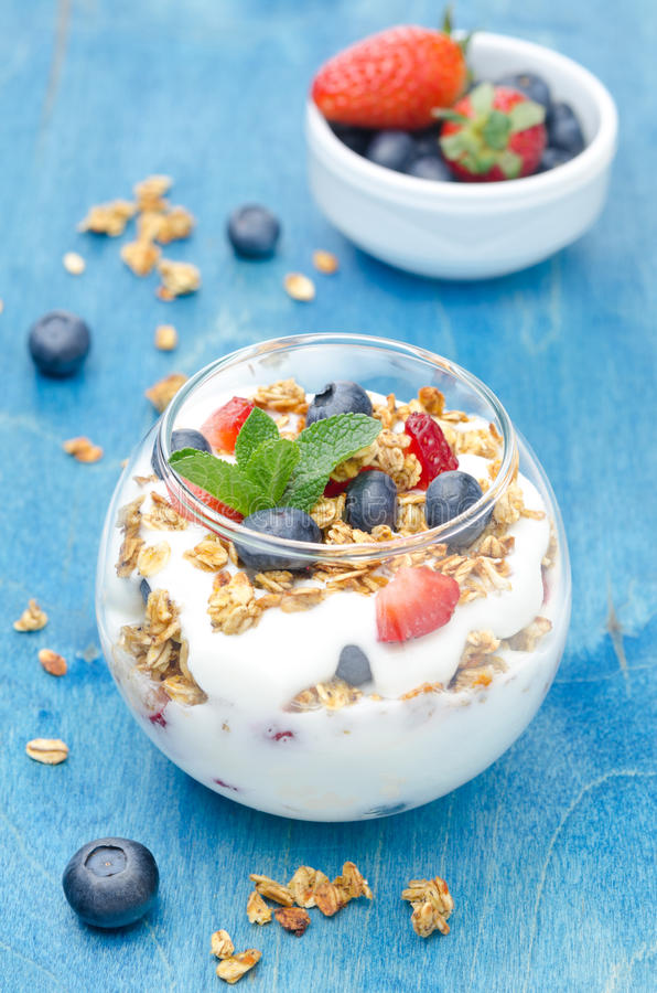 I lager efterrätt med yoghurt, granola, nya bär och en bunke royaltyfri foto