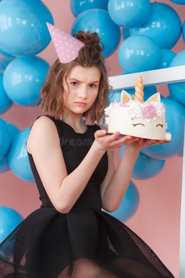 I lager kaka för lycklig tonårig flickainnehavenhörning som dekoreras med marängnärbild Rosa bakgrund med blåa bollar royaltyfria foton