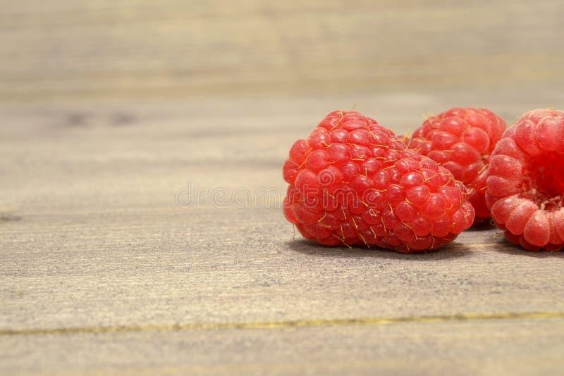 I lamponi dolci maturi sulla Tabella di legno contro il mucchio dell'estate fruttifica e bacche immagine stock
