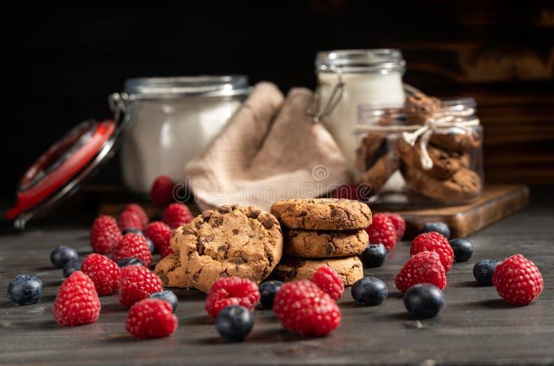 I lamponi, i mirtilli ed i biscotti a fuoco, il latte e la farina hanno sigillato i barattoli nel fondo fotografia stock