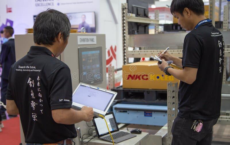 I lavoratori azionano il pannello di scaffale automatico fotografia stock libera da diritti