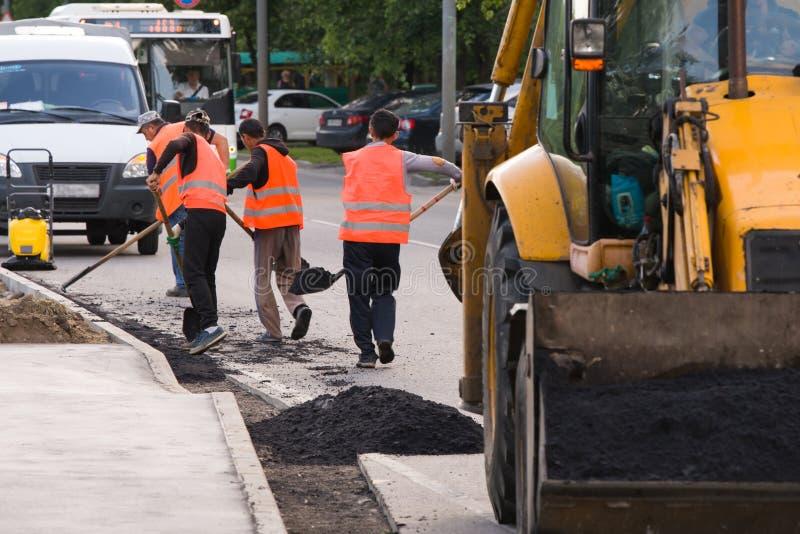 I lavoratori in camici hanno posto l'asfalto lungo il bordo sulla carreggiata fotografie stock
