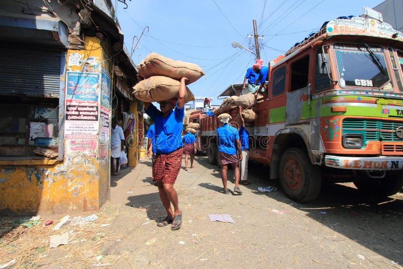 I lavoratori capi del carico che scaricano l'iuta insacca da un camion nel mercato fotografia stock