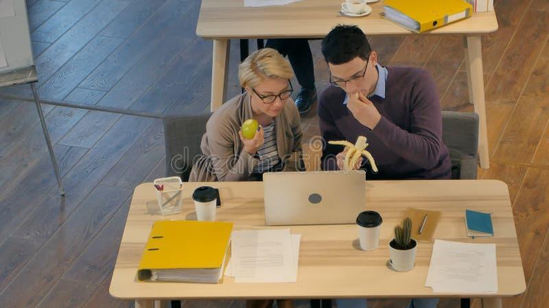 I lavoratori che godono del pranzo irrompono l'ufficio immagine stock
