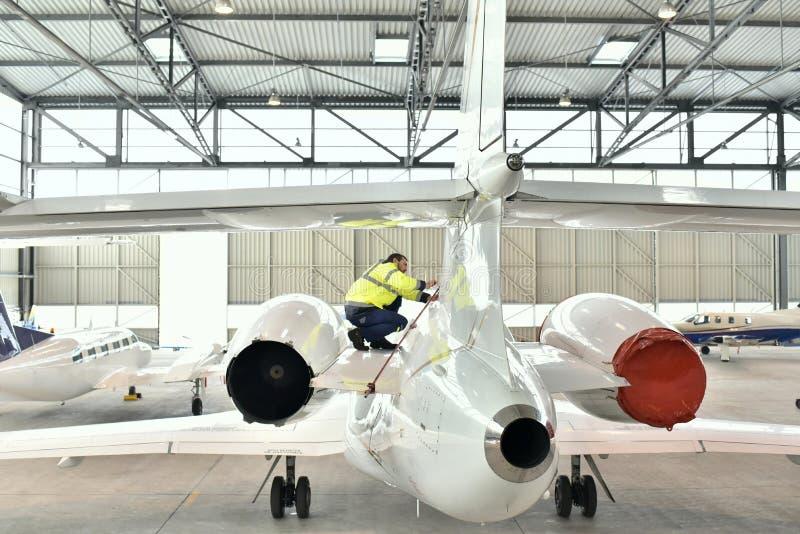 I lavoratori dell'aeroporto controllano un aereo per vedere se c'è la sicurezza in un capannone immagine stock libera da diritti