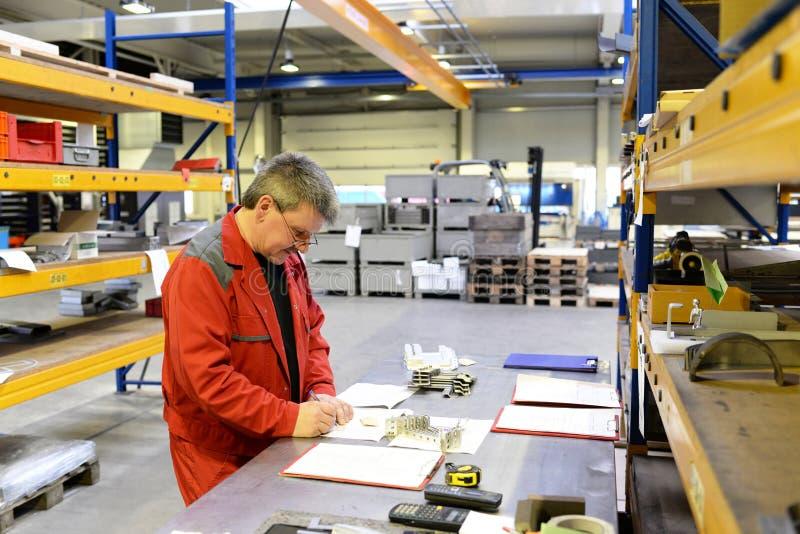 I lavoratori dell'industria ispezionano il pezzo da lavorare per accuratezza con lo strumento di misura fotografie stock libere da diritti