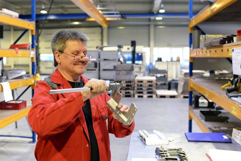 I lavoratori dell'industria ispezionano il pezzo da lavorare per accuratezza con lo strumento di misura immagini stock