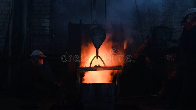 I lavoratori hanno versato il metallo fuso nella pianta Metraggio di riserva Lavoratori nel processo di controllo dei caschi e de immagini stock libere da diritti