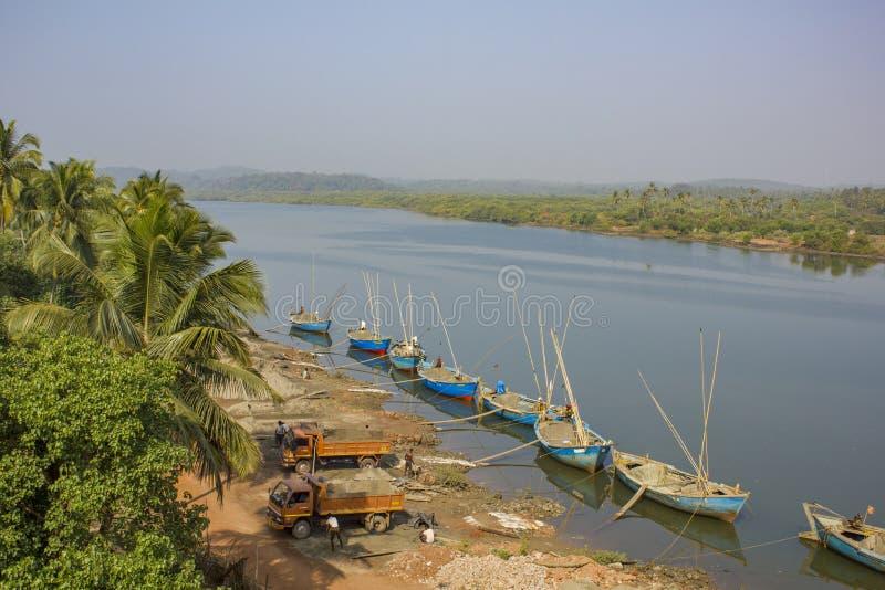 I lavoratori indiani estraggono la sabbia in un modo del fiume, le grandi barche blu fuori dal fiume ed i camion fotografia stock libera da diritti