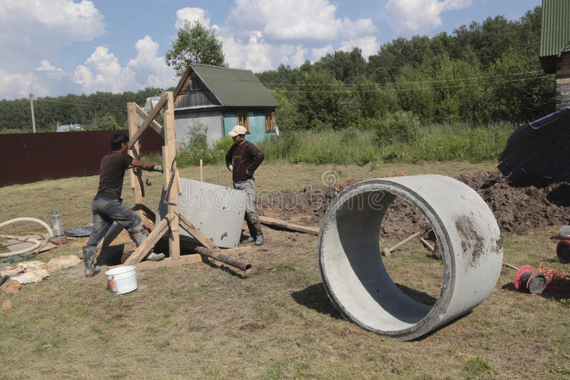 I lavoratori installano gli anelli concreti nel pozzo fotografia stock libera da diritti
