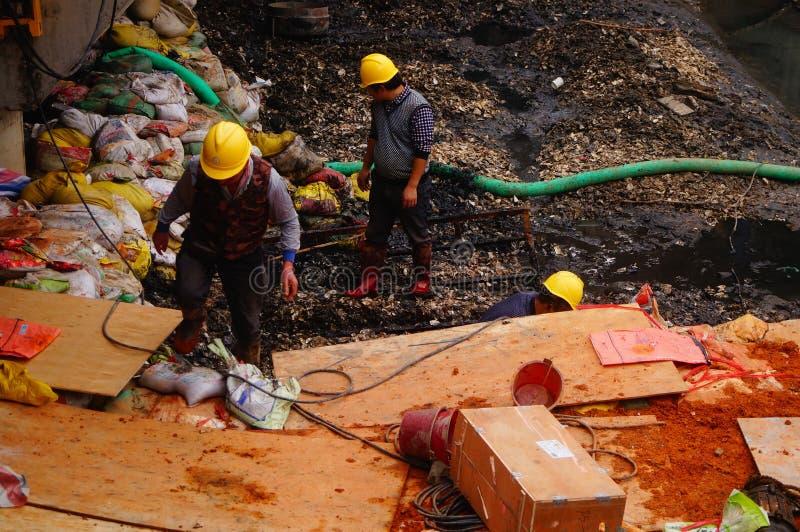 I lavoratori nella costruzione del fiume, sollevano uno scaffale del ferro fotografia stock libera da diritti