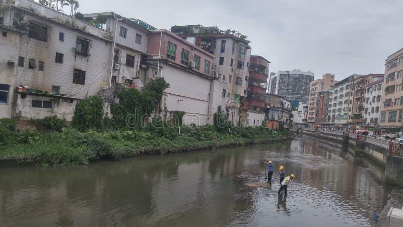 I lavoratori puliscono il limo nel fiume del xixiang a Shenzhen, Cina immagini stock libere da diritti
