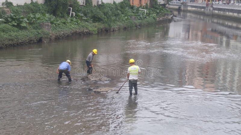 I lavoratori puliscono il limo nel fiume del xixiang a Shenzhen, Cina fotografia stock