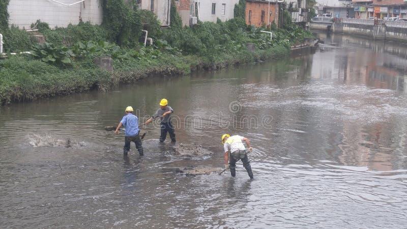 I lavoratori puliscono il limo nel fiume del xixiang a Shenzhen, Cina fotografia stock libera da diritti