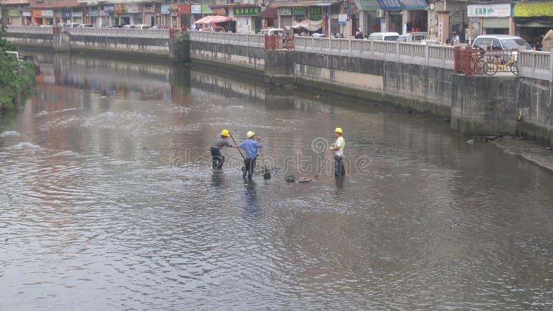 I lavoratori puliscono il limo nel fiume del xixiang a Shenzhen, Cina immagine stock libera da diritti