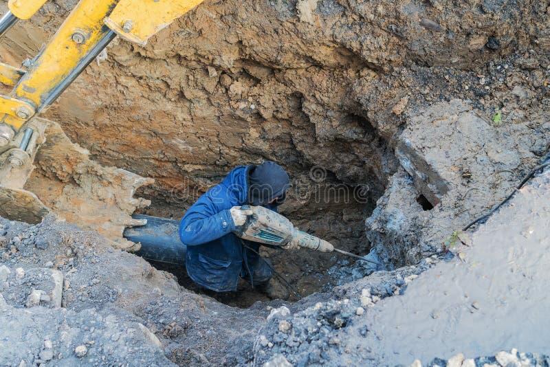 I lavoratori scavano il pozzo con un escavatore In costruzione fotografia stock libera da diritti