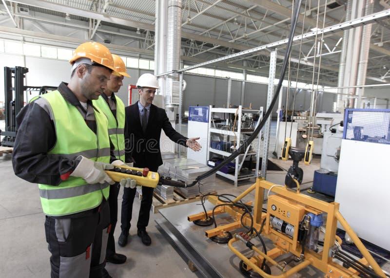 I lavoratori si avvicinano al dispositivo di sollevamento della lamina di metallo fotografie stock libere da diritti