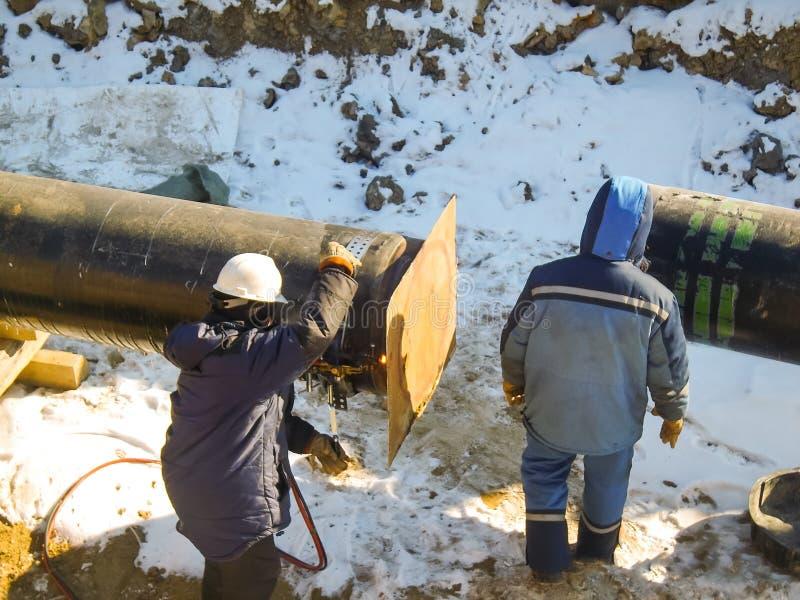 I lavoratori si sono impegnati nella costruzione della conduttura I saldatori costruiscono la conduttura Lavoro dell'installazion fotografie stock libere da diritti