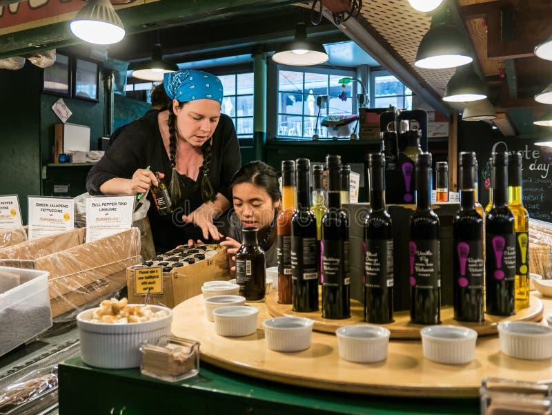 I lavoratori sistemano gli aceti al mercato pubblico del posto del luccio, Seattle fotografie stock