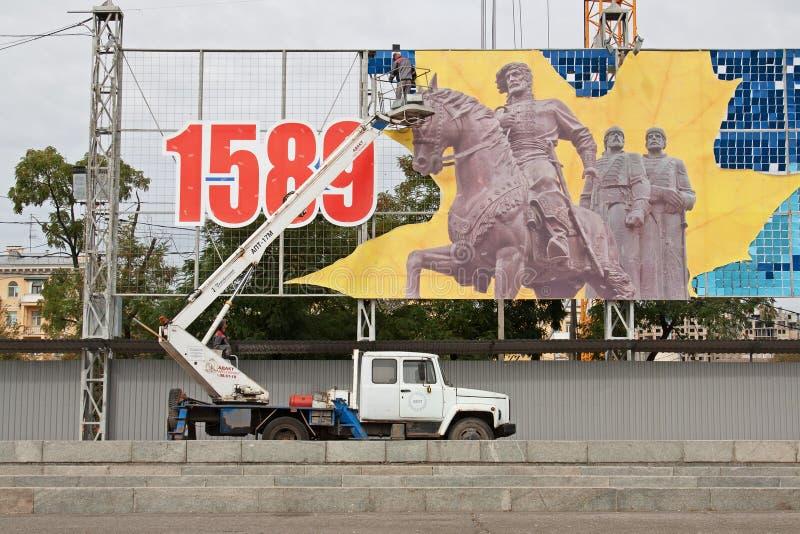 I lavoratori smantellano un pannello festivo al quadrato dei combattenti caduti a Volgograd immagini stock