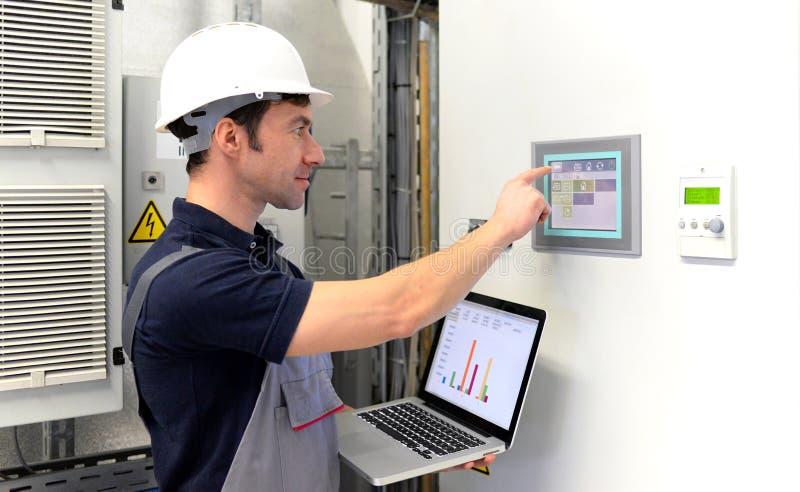I lavoratori in un impianto industriale controllano i sistemi con tecnico moderno fotografie stock libere da diritti