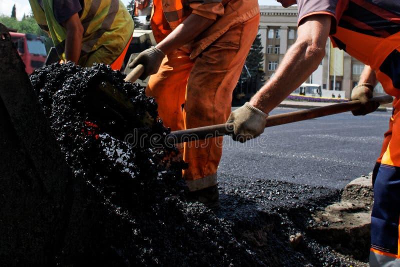 I lavoratori in uniforme arancione depongono l'asfalto in una strada della città Riparazione stradale immagini stock libere da diritti