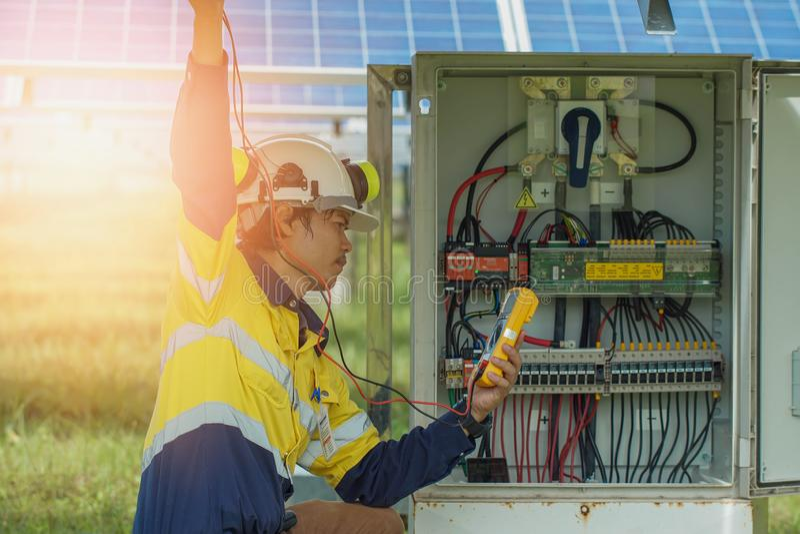 I lavoratori utilizzano Multimetro per misurare la tensione dei cavi elettrici prodotti a partire dall'energia solare per conferm immagini stock libere da diritti