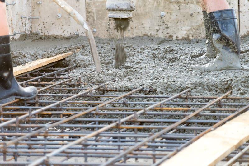 I lavoratori versano il fondamento per la costruzione di un edificio residenziale fotografie stock libere da diritti