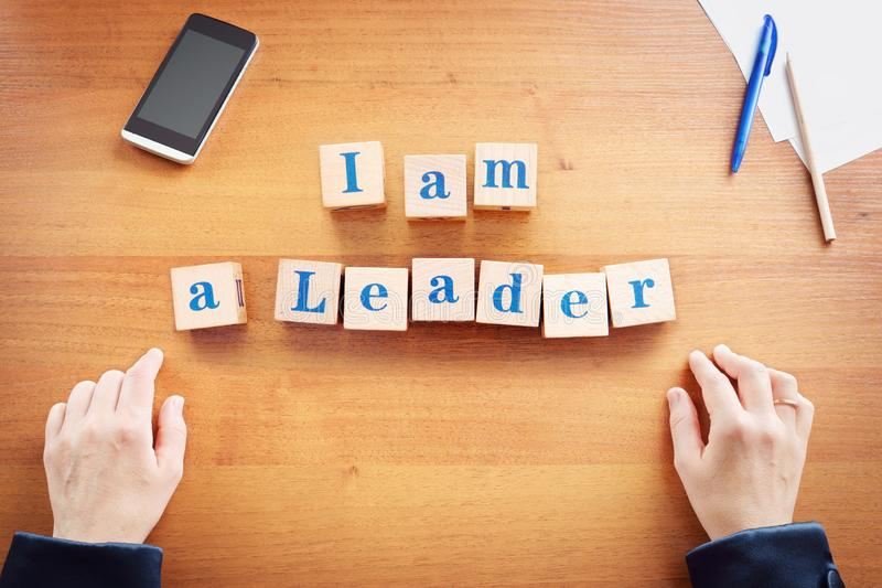 I am a leader. Business woman made text from wooden cubes. On a desk stock photography