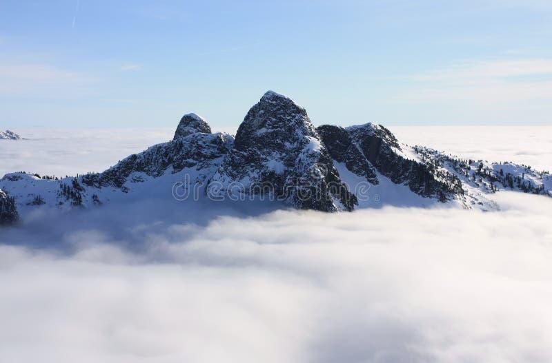 I leoni sopra le nuvole in montagne del nord della riva, BC, il Canada fotografia stock libera da diritti