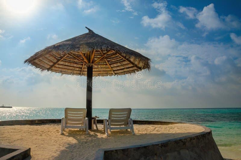 I lettini e gli ombrelli della palma su un fondo di cielo blu e di azzurro innaffiano, le Maldive fotografia stock