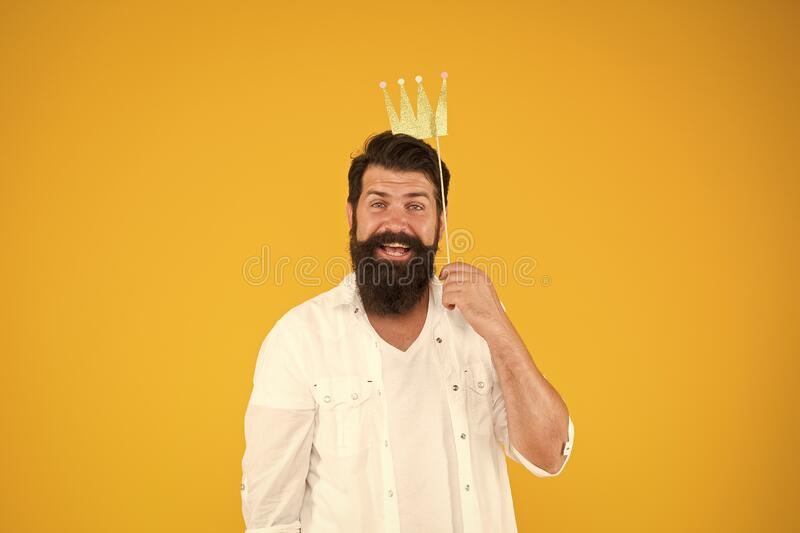 I like birthday surprises. royal style. brutal bearded man king. Costume party. happy birthday. hipster booth props. Yellow background. ready for fun. bearded royalty free stock photo