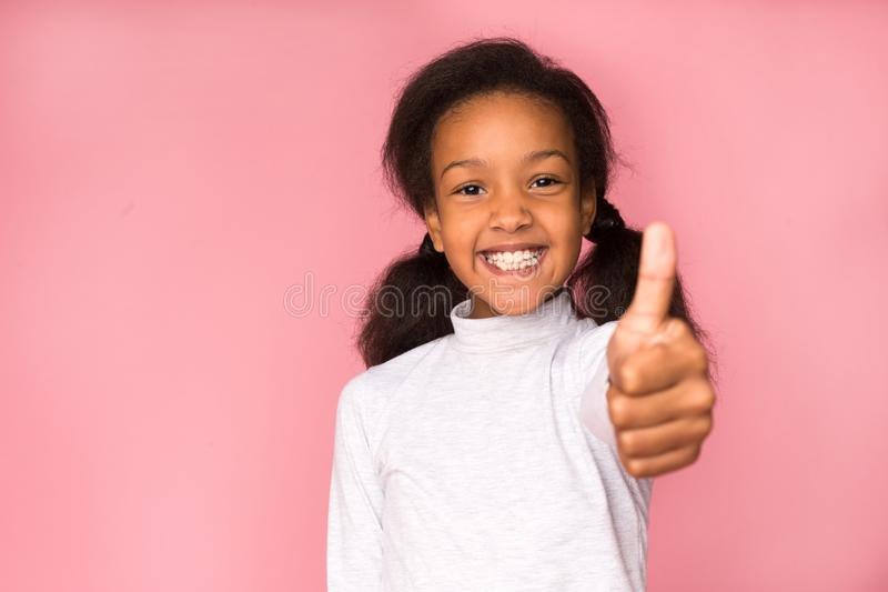 Happy girl showing thumb up on pink background royalty free stock photography