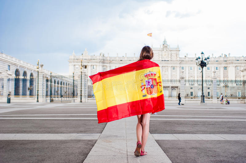 I like Madrid. Young woman in front of Palacio de Oriente - the Royal Palace of Madrid, holding a flag stock photo