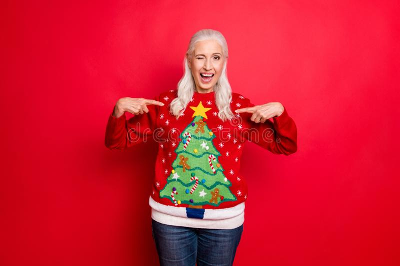 I like my jumper concept. Photo of blinking grey-haired positive hinting cheerful nice granny showing you her best with royalty free stock photos