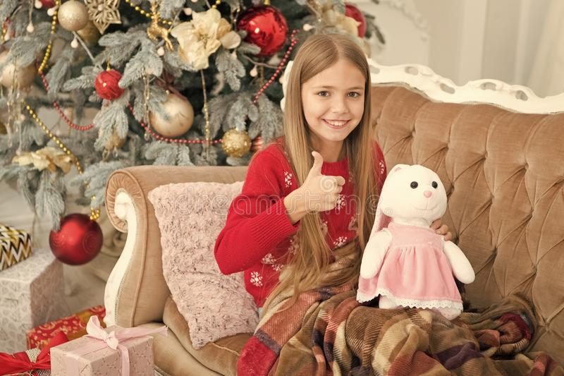 I like it very much. Little girl thumbs up to cute bunny at Christmas tree. Small girl hold rabbit toy. Little child stock photography