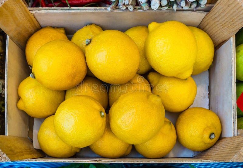 I limoni gialli maturi impilano in una scatola di legno sulla vendita, vista dalla cima Fresco e sano immagine stock