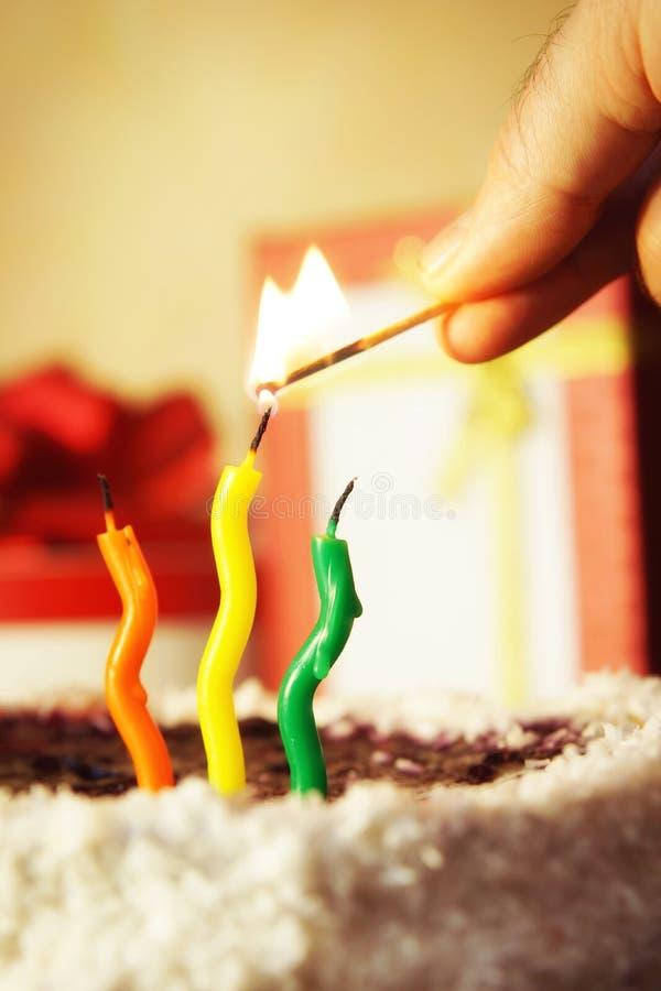I lits dell'uomo aumentano le candele su una torta di compleanno immagine stock