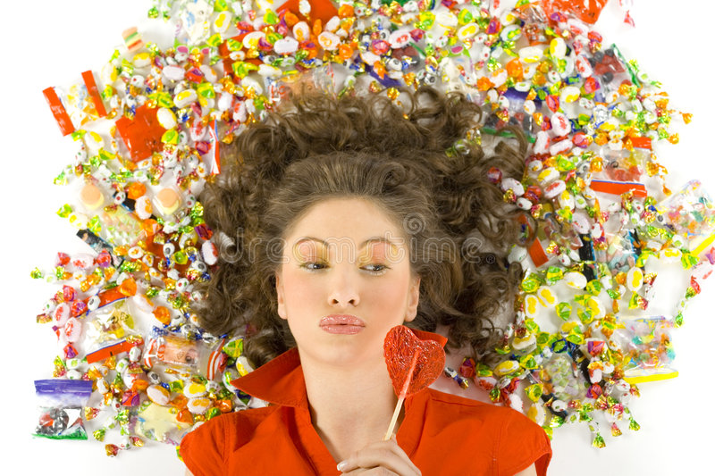 I'll eat you... Young, beautiful woman lying on floor among candys with lollypop in hand. Looking at lollypop, front view. White background stock images
