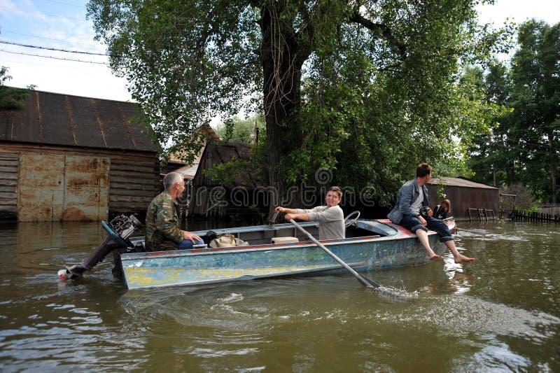 I locali si muovono intorno alle vie in barca L'Ob', che ha uscito dalle banche, ha sommerso le periferie della città immagine stock