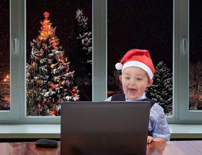 I locket av den Santa Claus pojken som ser en bärbar dator på bakgrunden av julgranen utanför fönstret arkivbild