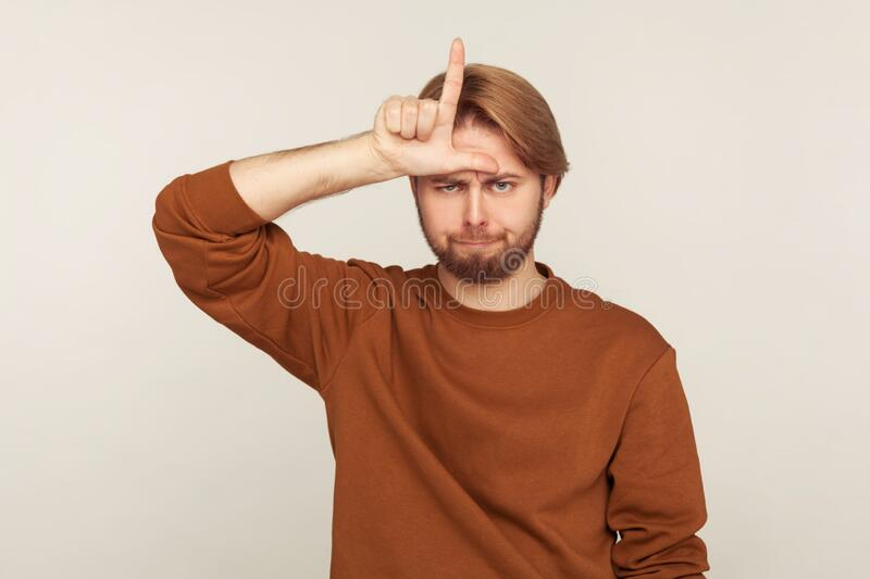 I am loser! Portrait of unhappy sad man with beard in sweatshirt standing with gloomy face and showing loser gesture. Unemployed or fired from job. indoor stock image