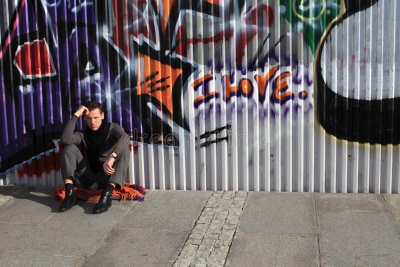 Man sitting near graffiti wall royalty free stock images