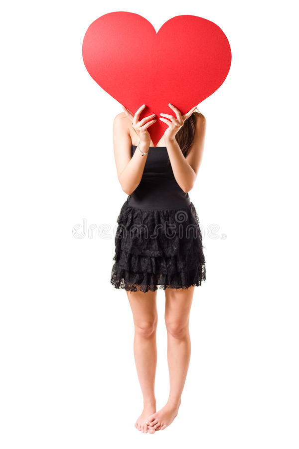 I love... Beautiful young brunette girl holding big red heart, isolated on white background royalty free stock photo